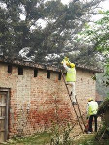 Die Einzelteile des Microgrid kommen via Bambusleiter aufs Dach.