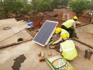 Das Solarmodul für das Microgrid wird am Gestell angebracht, ausgerichtet und mit einem einfachen Fundament am Hausdach befestigt.