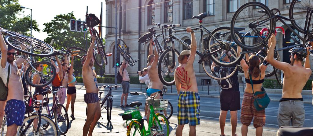 Bikini bike ride Berlin VCD Menschen halten Fahrräder über Köpfe
